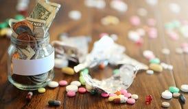 Лекарства и монетки в стеклянном опарнике на деревянном поле Карманные сбережения Стоковое Изображение RF