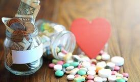 Лекарства и монетки в стеклянном опарнике на деревянном поле Карманные сбережения Стоковые Изображения RF