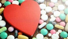 Лекарства и монетки в стеклянном опарнике на деревянном поле Карманные сбережения Стоковая Фотография