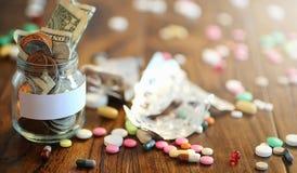 Лекарства и монетки в стеклянном опарнике на деревянном поле Карманные сбережения Стоковое Фото