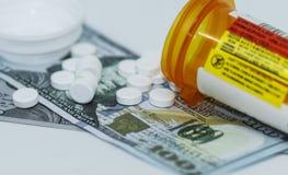 Лекарства разливают вне на 100 долларовых банкнотах стоковые фотографии rf