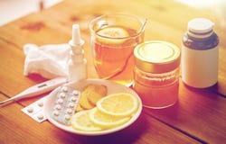 Лекарства, термометр, мед и чашка чаю на древесине Стоковые Фото