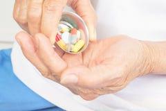 Лекарство в руке и старухах стоковая фотография