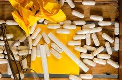 Лекарство капсулы с желтыми примечанием и сигаретой стоковые изображения