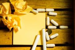 Лекарство капсулы с желтыми примечанием и сигаретой стоковое изображение