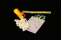 Лекарство сказано по буквам вне с плитками, разлитыми пилюльками рецепта на пусковой площадке рецепта на черной предпосылке Стоковые Фотографии RF