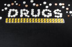 ` Лекарств ` слова положено из пилюлек на темную предпосылку с пакетами пилюлек, взгляд сверху стоковое фото rf
