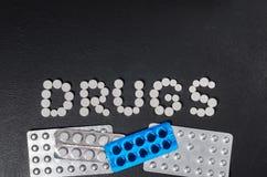 ` Лекарств ` слова положено из пилюлек на темную предпосылку с пакетами пилюлек стоковое фото rf