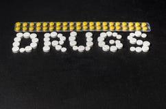 ` Лекарств ` слова положено из пилюлек на темную предпосылку с пакетами пилюлек стоковая фотография rf
