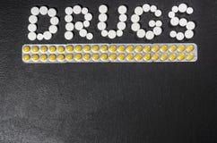 ` Лекарств ` слова положено из пилюлек на темную предпосылку с пакетами пилюлек стоковые фото