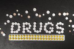 ` Лекарств ` слова положено из пилюлек на темную предпосылку с пакетами пилюлек стоковое изображение