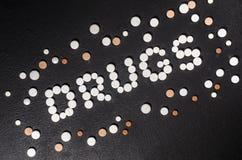 ` Лекарств ` слова положено из таблеток на темную предпосылку с разбросанными таблетками стоковые изображения