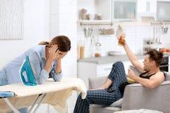 Ленивый супруг смотря ТВ и его утомленная жена стоковые изображения