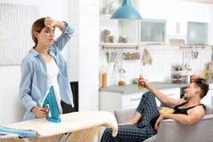 Ленивый супруг смотря ТВ и его утюжить жены стоковые изображения