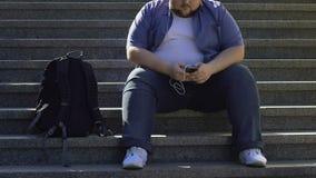Ленивый человек сидя на лестницах, слушая к музыке и беседуя с друзьями онлайн сток-видео