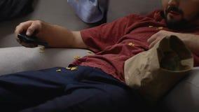Ленивый человек смотря ТВ съесть закуски на пакостной софе в живущей комнате, образе жизни видеоматериал