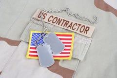 Лента ветви ПОДРЯДЧИКА США с регистрационными номерами собаки и заплата флага на форме пустыни Стоковая Фотография