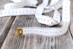 Лента для измерений тела на деревянной предпосылке Стоковая Фотография RF