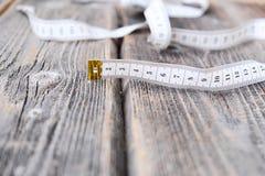 Лента для измерений тела на деревянной предпосылке Стоковые Фотографии RF