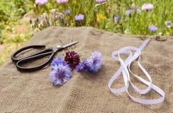 Лента и ножницы с свеже отрезанными cornflowers на hessian стоковая фотография