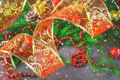 Лента красного рождества орнаментальная от organza окруженного елью разветвляет Стоковое Изображение