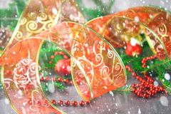 Лента красного рождества орнаментальная от organza окруженного елью разветвляет Стоковые Фото