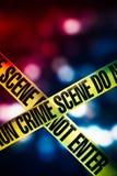 Лента места преступления с красными и голубыми светами на предпосылке стоковое фото