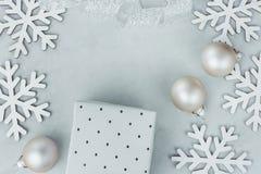 Лента подарочной коробки безделушек хлопьев снега состава Нового Года рождества белым завитая серебром на серой каменной предпосы Стоковые Изображения RF