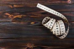 Лента поднимающего вверх портноя конца измеряя на предпосылке деревянного стола Белая измеряя лента отмелый dept поля Стоковые Фото