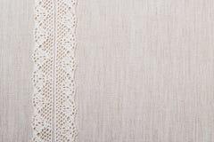 Лента шнурка на предпосылке linen ткани Стоковое Изображение
