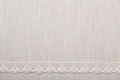 Лента шнурка на предпосылке linen ткани Стоковая Фотография