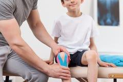 Лента Kinesiology на колене Стоковое Изображение