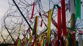 Ленты молитве прикрепленные к загородке колючей проволоки около границы между севером и югом Северной Кореей Стоковое Изображение