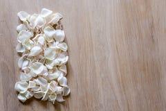 Лепестки белой розы на деревянной предпосылке с космосом для вашего текста Стоковая Фотография RF