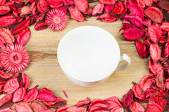 Лепестки роз на естественной предпосылке деревянного стола Полюбите шаблон для цветков пинка дня валентинок вокруг Белая чашка ча Стоковые Фотографии RF