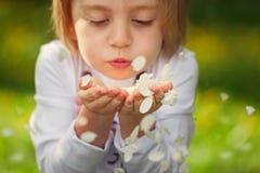 Лепестки цветка девушки портрета крупного плана дуя в парке на летний день стоковое изображение rf