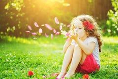 Лепестки цветка маленькой девочки дуя от ее рук в солнечном свете Стоковые Фото