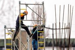 Леса металла строения 2 работников на строительной площадке стоковое фото rf