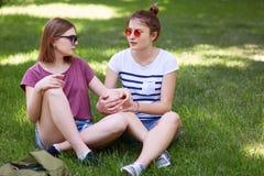 Лесбиянки женщин имеют потеху совместно пока сидите пересеченные ноги на зеленой траве, посмотрите с влюбленностью на одине друго стоковое фото
