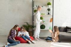 Лесбосская молодая семья в случайных одеждах имея потеху совместно дома стоковая фотография