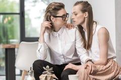 Лесбосские пары сидя совместно и смотря один другого пока выпивающ кофе Стоковое Фото