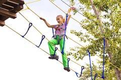 Лестницы девушки взбираясь на высоте в парке атракционов Стоковые Фотографии RF
