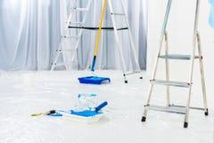 лестницы и щетки ролика краски в голубой краске стоковые фотографии rf