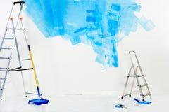 лестницы и щетки ролика краски в сини стоковое изображение