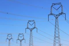 Лес высоковольтных башен под голубым небом Стоковые Изображения