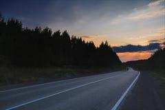 Лес осени с проселочной дорогой на заходе солнца Красочный ландшафт с деревьями, сельская дорога, солнце в падении стоковая фотография