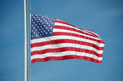 Летание американского флага на половинном рангоуте против голубого неба Стоковая Фотография