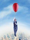 Летание бизнесмена на большом баллоне стоковое изображение