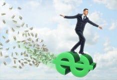 Летание бизнесмена на большом знаке доллара стоковые изображения