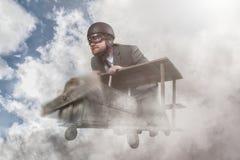 Летание бизнесмена с деревянным самолетом игрушки стоковое фото rf